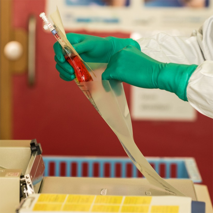 Pharmacist packing Cytostatics with latex gloves and clean room uniform